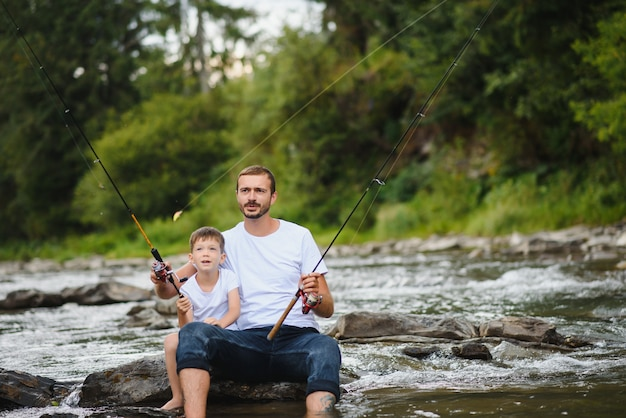 Ojciec uczy syna łowić ryby w rzece