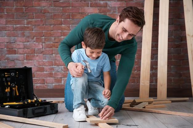 Ojciec uczy syna wbijania gwoździ w warsztacie