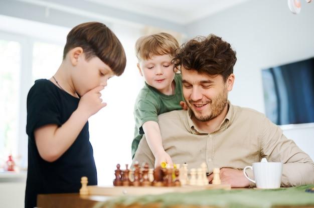 Ojciec uczy synów grać w szachy