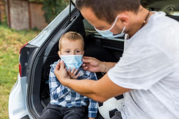 Ojciec układa synowi maskę medyczną