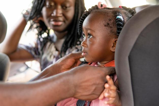 Ojciec umieszcza córkę w foteliku samochodowym dla dzieci