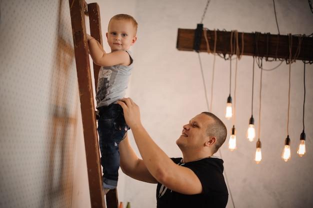 Ojciec w domu pomaga swojemu małemu synowi wspinać się po drabinie