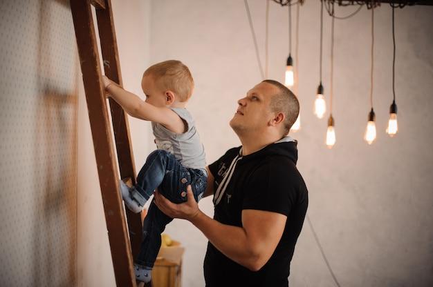 Ojciec w domu pomaga swojemu małemu synowi wspinać się powoli po drabinie