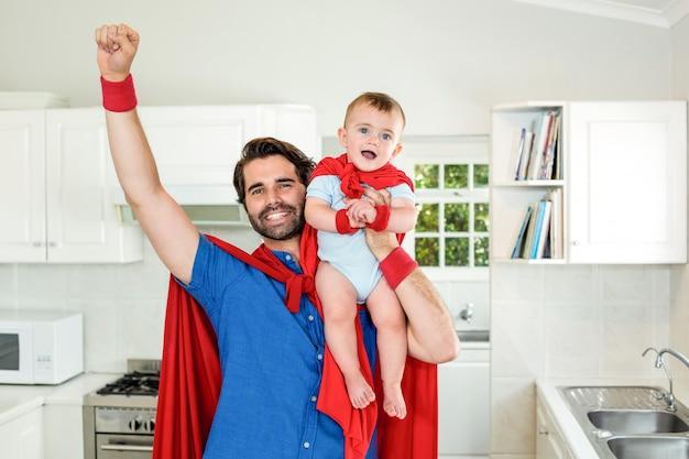 Ojciec w kostium superbohatera podnoszenia syna w kuchni
