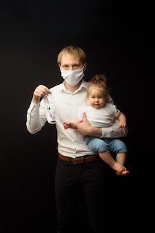 Ojciec w medycznej masce trzyma swoją małą córeczkę. koncepcja ochrony dzieci podczas epidemii koronawirusa