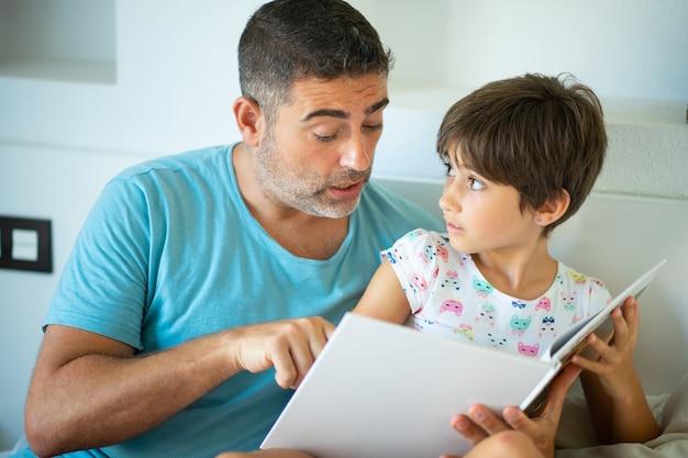 Ojciec w średnim wieku z ośmioletnią córką za pomocą cyfrowego tabletu w sypialni.