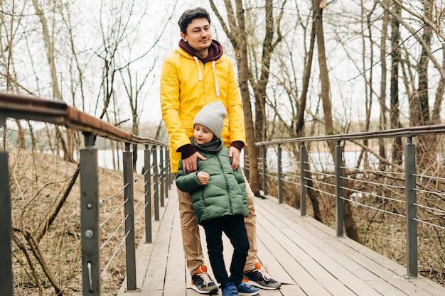 Ojciec w żółtym płaszczu przeciwdeszczowym i syn bawią się w lesie szczęśliwa rodzina z dzieckiem chłopiec bawi się i
