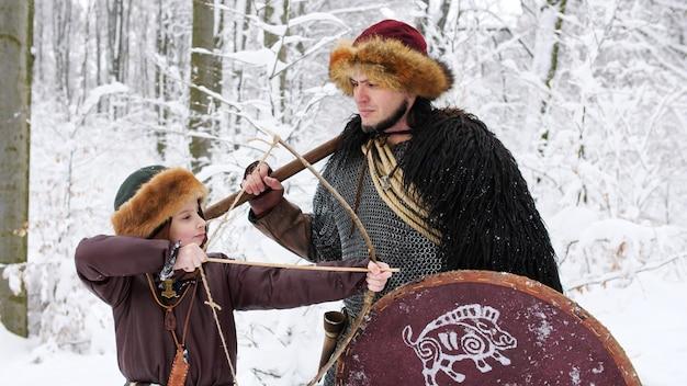 Ojciec wiking uczy syna łucznictwa w zimowym lesie. ubrani byli w średniowieczne ubrania.