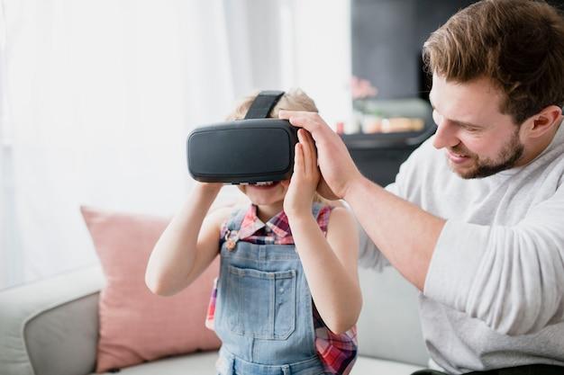 Ojciec wkłada okulary vr na córkę