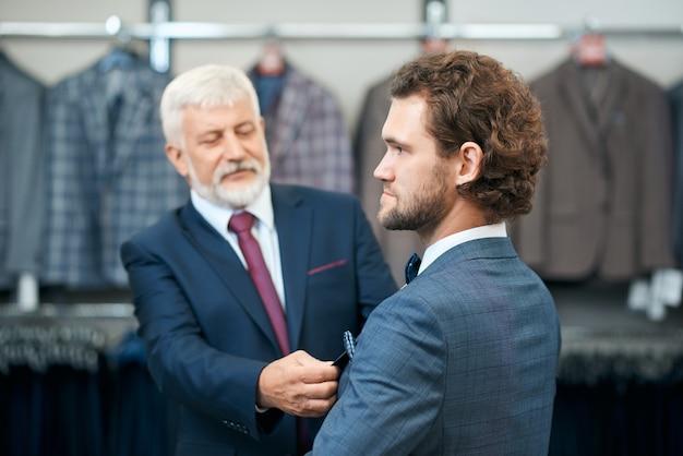 Ojciec wybiera kostiumy dla syna w sklepie.