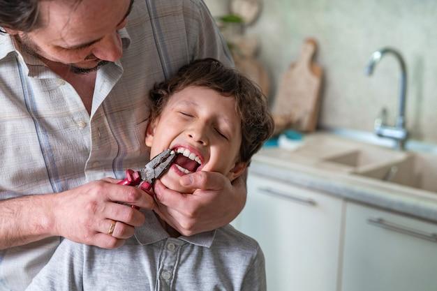 Ojciec wyciągnął mały ząb syna za pomocą narzędzia do budowy szczypiec