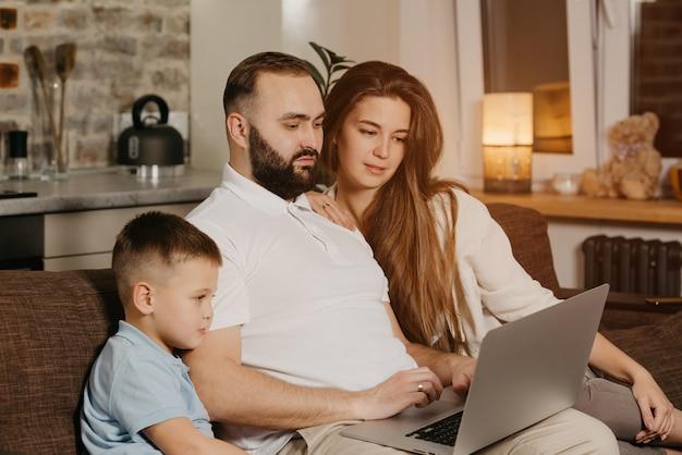 Ojciec z brodą opowiada o swoich osiągnięciach w pracy synowi i żonie w domu. młoda rodzina na kanapie wieczorem. tata pracuje zdalnie na laptopie między krewnymi