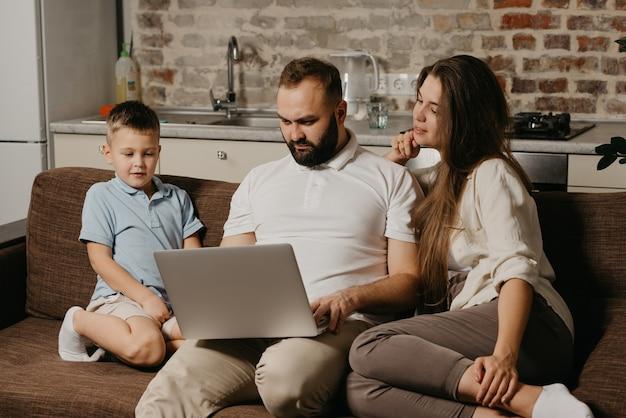 Ojciec z brodą pracuje zdalnie na laptopie, podczas gdy jego syn i żona wpatrują się w ekran. rodzina na kanapie wieczorem. tata pracuje online na komputerze między krewnymi w domu