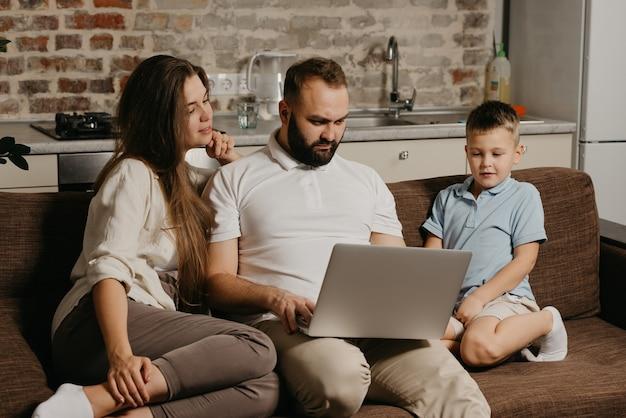 Ojciec z brodą pracuje zdalnie na laptopie, podczas gdy jego syn i żona wpatrują się w ekran