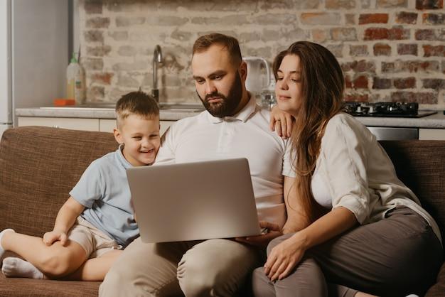 Ojciec z brodą pracuje zdalnie na laptopie, podczas gdy jego szczęśliwy syn i żona wpatrują się w ekran. tata pracuje wieczorem na komputerze między krewnymi na kanapie w domu