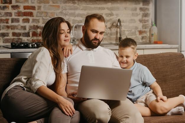 Ojciec z brodą pracuje zdalnie na laptopie, podczas gdy jego szczęśliwy syn i żona wpatrują się w ekran