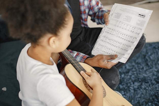 Ojciec z córką na kanapie. dziewczyna trzyma gitarę. nauka gry na gitarze.