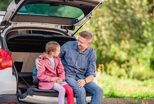 Ojciec z córką siedzącą na bagażniku samochodu po szkole
