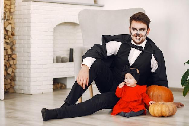 Ojciec z córką w kostiumach i makijażu. rodzina przygotowuje się do świętowania halloween.