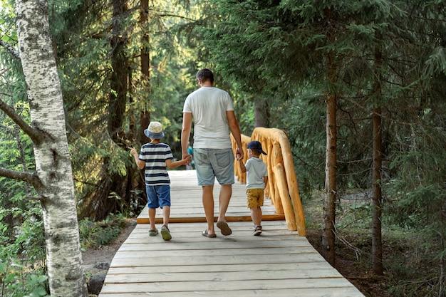 Ojciec z dwójką dzieci spaceruje po parku na drewnianej ścieżce