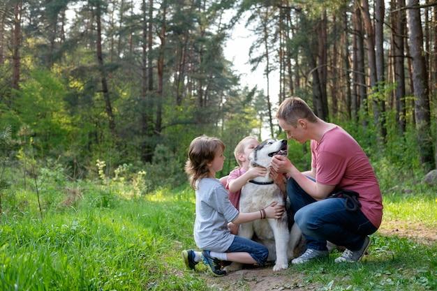 Ojciec z dwoma małymi synami spaceruje z psem w letnim lesie i dobrze się bawi