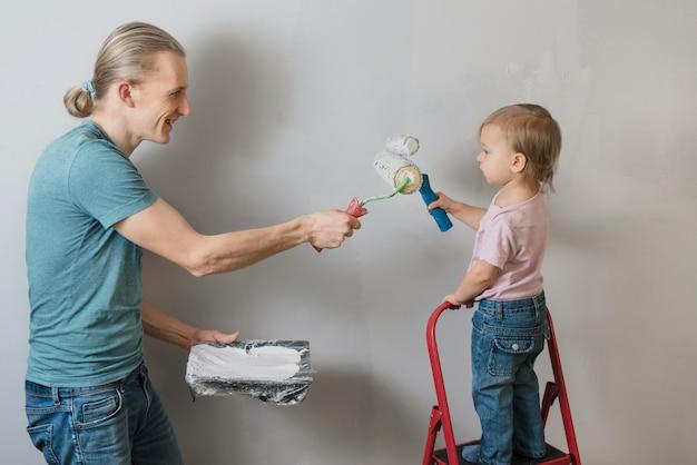 Ojciec z dzieckiem robi dekorację i przeprojektowanie w pokoju