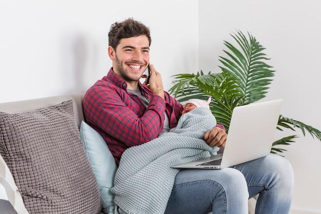Ojciec z dzieckiem rozmawia przez telefon i za pomocą laptopa