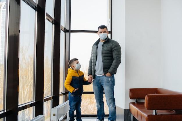 Ojciec z dzieckiem stoi w masce podczas kwarantanny. pandemia, koronawirus