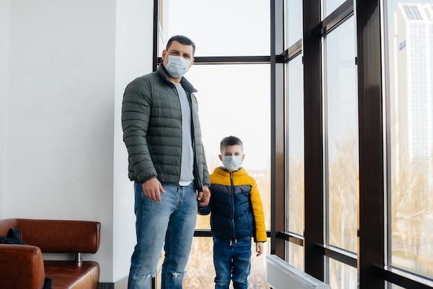 Ojciec z dzieckiem stoi w masce podczas kwarantanny. pandemia, koronawirus.