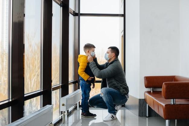 Ojciec z dzieckiem stoi w masce podczas kwarantanny