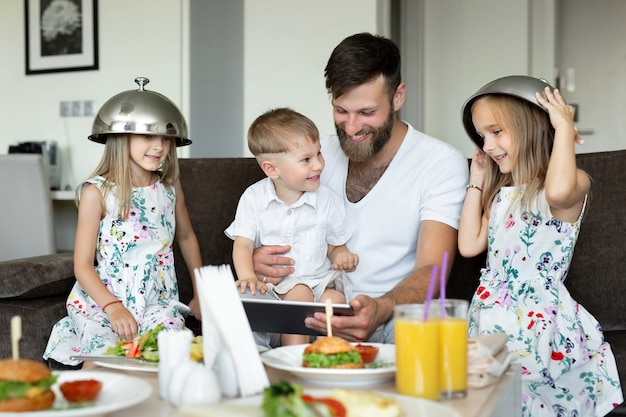 Ojciec z dziećmi je śniadanie w pokoju hotelowym i baw się, dogadza.