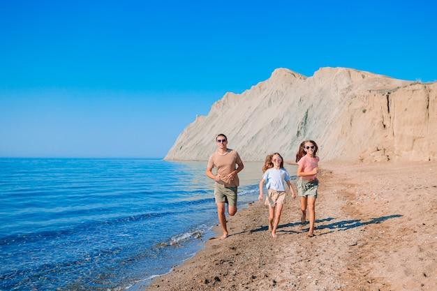 Ojciec z dziećmi na plaży, ciesząc się latem. rodzinne wakacje