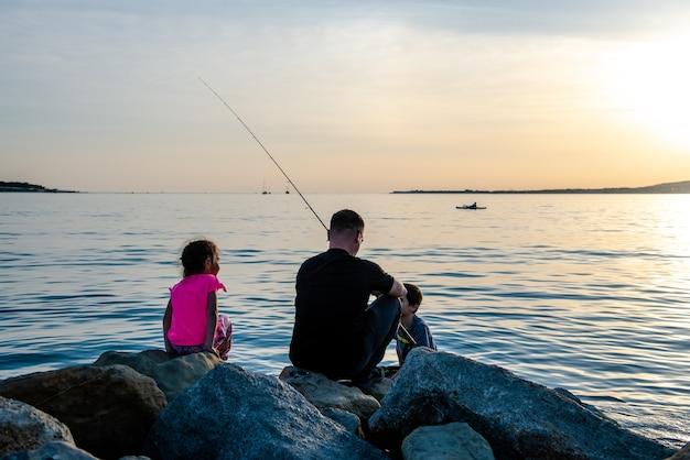 Ojciec z dziećmi na wyprawie wędkarskiej nad morzem dzieci łowią ryby nad klifem w morzu
