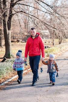 Ojciec z dziećmi spacerujący po parku