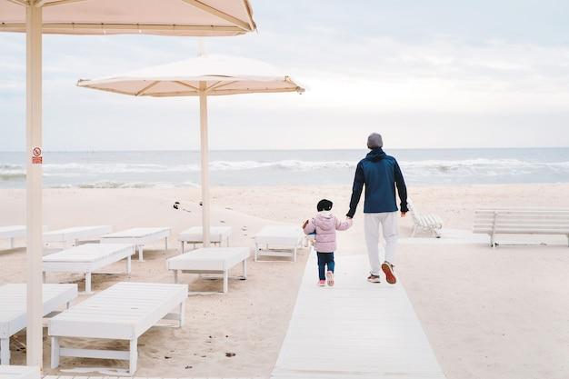 Ojciec z dziewczynką idącą na plażę jesienią