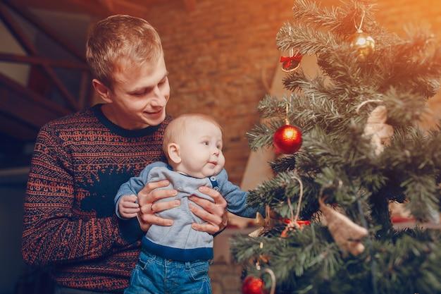 Ojciec z jego dzieckiem w ramionach patrząc na drzewo ozdób choinkowych