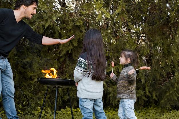 Ojciec z jej córką cieszy się blisko grilla przy outdoors