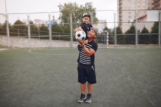 Ojciec z małym synem bawić się piłkę nożną