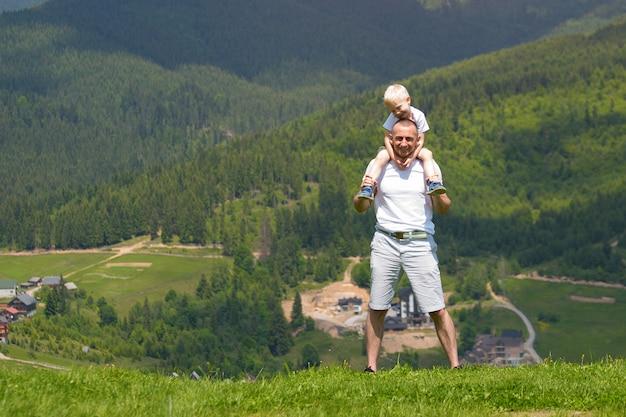 Ojciec z małym synem na ramionach. góry letni słoneczny dzień.