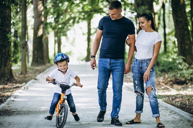 Ojciec z matką uczy ich małego syna jeździć na rowerze
