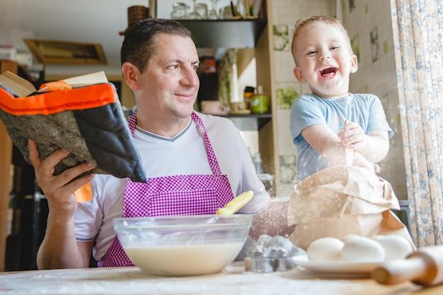 Ojciec z młodym synem przy kuchennym stole przygotowujący ciasto