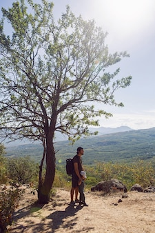 Ojciec z plecakiem i synem stoi latem obok drzewa na górze na krymie