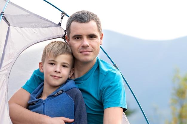 Ojciec z synem dziecko odpoczywa razem w namiocie w górach latem. koncepcja aktywnego wypoczynku rodzinnego.