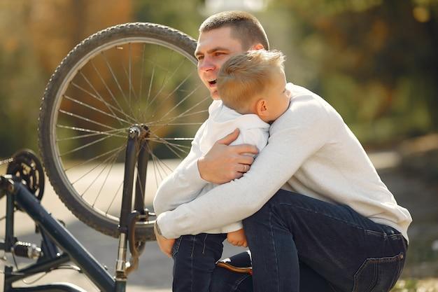 Ojciec z synem naprawia rower w parku