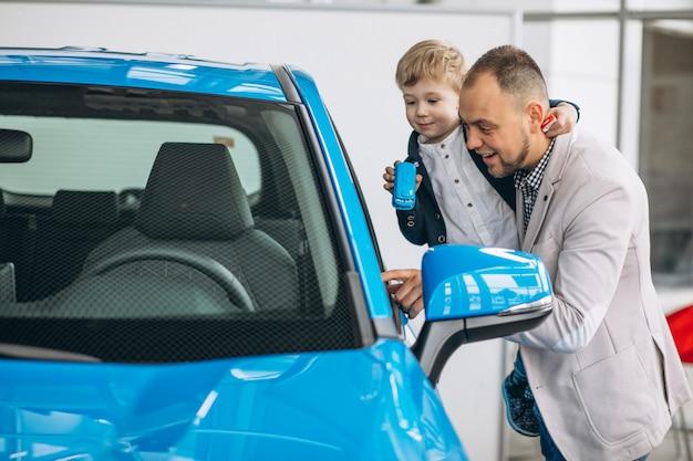 Ojciec z synem patrzeje samochód w samochodowej sala wystawowej