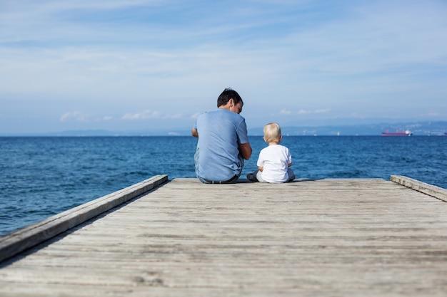 Ojciec z synem siedzący na morskim molo tło rodzinne rodzic i dziecko razem
