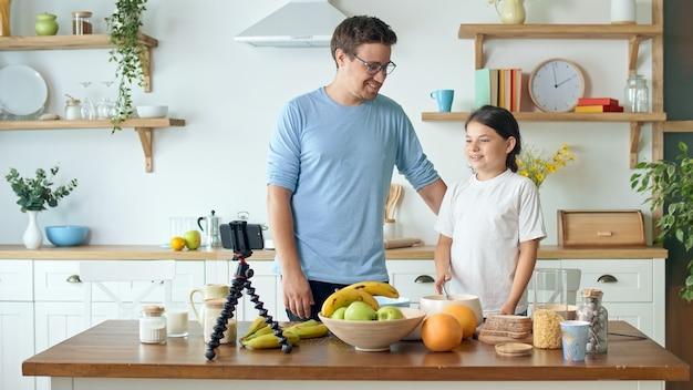 Ojciec z uroczą córką bloguje o gotowaniu. blog wideo o zdrowym odżywianiu. ojciec z dzieckiem ogląda internetowy blog wideo. ojciec uczy córkę gotować.