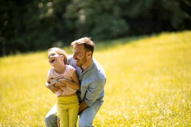 Ojciec z uroczą małą córeczką bawi się na trawie w parku