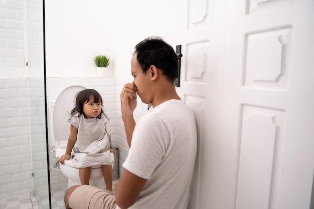 Ojciec zamyka nos, towarzysząc córce, aby wypróżnić się