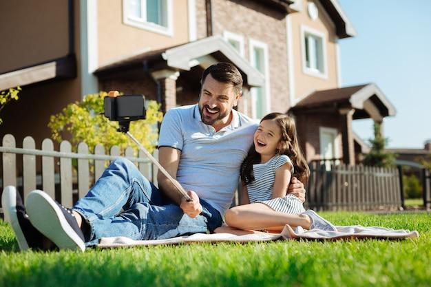 Ojcowska miłość. przyjemny młody człowiek siedzący na dywanie obok swojej córeczki, przytulający ją i śmiejący się przy selfie kijem do selfie